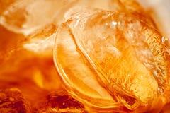 En orange guld- tonad bakgrund som skapas från insidan av ett exponeringsglas av cola med is arkivfoto