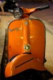 En orange Vespamotorcykel, retro stil Arkivbild