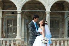 En paar die elkaar op oud kasteel als achtergrond koesteren kijken Stock Fotografie