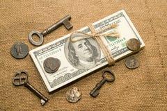 En packe av dollar, mynt och tangenter på en gammal torkduk Arkivbilder