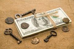 En packe av dollar, mynt och tangenter på en gammal torkduk Royaltyfri Foto