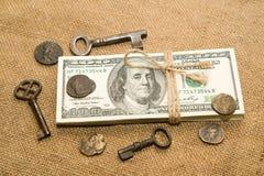 En packe av dollar, mynt och tangenter på en gammal torkduk Arkivfoto