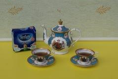 En packe av original- engelska Tetleys teabags bredvid engelska tekoppar med tefat och tekannan, fint benporslinporslin royaltyfri bild
