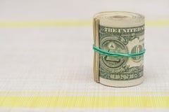 En packe av pengar som vrids in i en packe och binds med en grön gummiband Royaltyfria Bilder