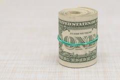 En packe av pengar som vrids in i en packe och binds med en grön gummiband Arkivfoton