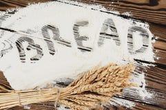 En packe av vete- och vallmo- och handskriftordet BRÖD på mjöl på gamla träplankor Arkivfoton