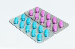 En packe med rosa färger och en packe med blåa avlånga preventivpillerar som isoleras på en vit bakgrund Royaltyfria Foton