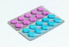 En packe med rosa färger och en packe med blåa avlånga preventivpillerar som isoleras på en vit bakgrund Arkivfoton