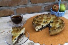 En paj, en skiva av äppelpajen med körsbär och valnötter, en kopp te och äpplen i en korg är på tabellen fotografering för bildbyråer