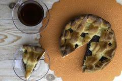 En paj, en skiva av äppelpajen som fylls med körsbär och valnötter, och en kopp te är på tabellen royaltyfri fotografi