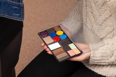 En palett av skuggor med olika färger av produkten i händerna av en modell i en skönhetstudio, som makeup appliceras med arkivfoton