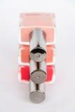 En palett av spikar polermedelflaskor på en vit bakgrund Royaltyfri Fotografi