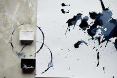 En palett av svartvit målarfärg ett ark av vitt konstpapper med svart färgfärgpulver Royaltyfri Foto
