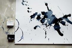 En palett av svartvit målarfärg ett ark av vitt konstpapper med svart färgfärgpulver Royaltyfria Bilder