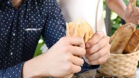 En panadería Ciérrese para arriba de las manos masculinas que rasgan el pan francés para arriba Baguette de rasgado del hombre po almacen de video