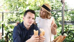En panadería Hombre hermoso joven que rasga el pan francés para arriba Baguette de rasgado del hombre por la mitad Una pequeña mu metrajes