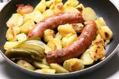 En panna med korvar och potatisar Royaltyfria Bilder