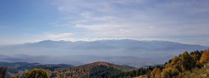 En panorama av bergkonturn med mist arkivfoton