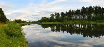 En panorama- bild SOMMAREN landskap Afton på floden Reflexion av moln och himmel i vattnet Royaltyfria Bilder
