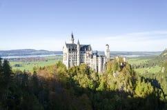 En panoramautsikt av den Neuschwanstein slotten med träd i den Bayern Tyskland arkivfoton