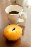 En paper kopp av kaffe och bagerit Arkivfoto