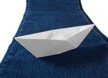 Pappers- fartyg på jeans Arkivbild