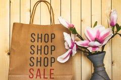 En pappers- shoppingpåse nära en blomma Fotografering för Bildbyråer
