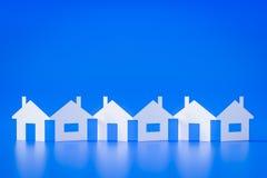 En pappers- utklipprad av hus slösar bakgrund Arkivfoto