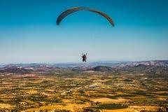 En paraglider flyger över pittoreska fält i bakgrunden av blå himmel Royaltyfri Bild