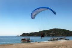 En paragliding kommer in att landa på den Oludeniz stranden på turkoskusten av Turkiet arkivbilder