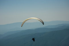 En paraglidingtandemcykel flyger över en bergdal på en solig summa arkivfoto