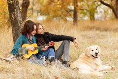 En parc d'automne près d'un arbre un jeune ajouter à un chien, une fille jouant la guitare photo stock