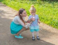 En parc, le bébé et la maman soufflent des bulles photographie stock