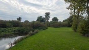 En parkera på sena September, sikt av en flod Arkivfoto