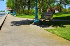 En parkerabänk längs kusten av Lake Michigan Arkivbild