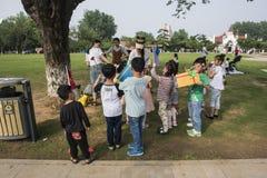 En parque del lago Xuanwu, un grupo de niños que estudian las bellas arte se alinea para esperar a profesores para enviar premios fotografía de archivo