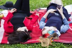 En partageant des secrets pendant l'après-midi dehors reposez-vous Photo stock