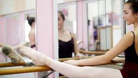 En pasillo de baile, bailarina joven en el leotardo negro que estira en la barra, colocando elegante la barra cercana en el espej almacen de video