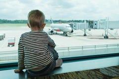 En pasillo del aeropuerto el niño mira el avión a través de ventana imágenes de archivo libres de regalías