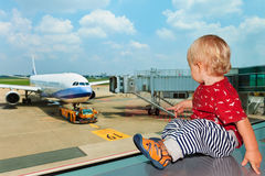 En pasillo del aeropuerto el niño mira el avión a través de ventana fotografía de archivo libre de regalías