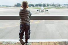 En pasillo del aeropuerto el niño mira el avión a través de ventana fotos de archivo