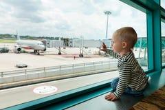 En pasillo del aeropuerto el niño mira el avión a través de ventana foto de archivo