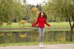 En passform och en idrotts- ung kvinna hoppar over med ett hopprep i parkera Royaltyfri Foto