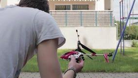 En patio el individuo barbudo sostiene el helicóptero del juguete con teledirigido en luz del día metrajes
