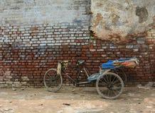 En pedicabparkering på gatan med den gamla väggen i Amritsar, Indien Royaltyfri Foto