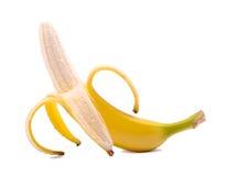 En peelea i en halv banan som isoleras på en vit bakgrund Söt, ny, mogen halva-skalad banan Begrepp för tropisk frukt Fotografering för Bildbyråer
