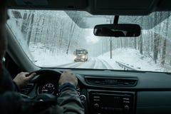 En pendlare som kör i en vintersnöstorm arkivfoto