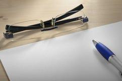 En penna på en vitbok och ett par av exponeringsglas Royaltyfri Foto