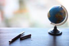En penna på skrivbordet och ett litet jordklot Royaltyfria Bilder