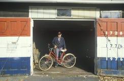 En pensionär i hans patriotiska themed garage, värma sig Ridge som är ny - ärmlös tröja Royaltyfri Foto